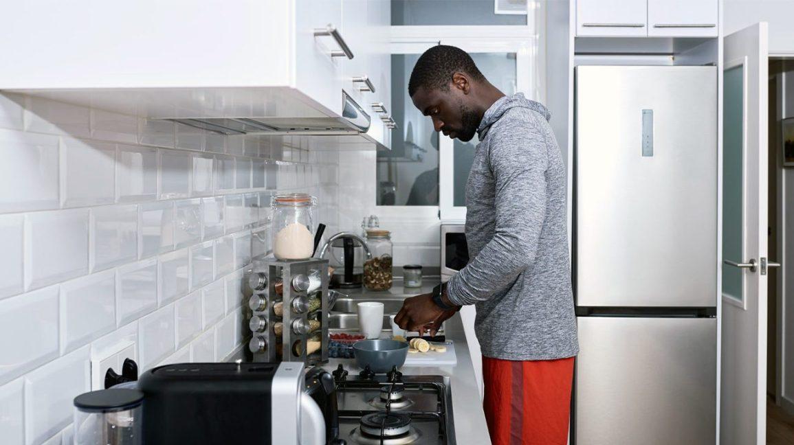 Homme sportif préparant un repas en cuisine