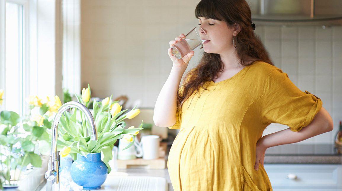 Femme enceinte buvant un verre d'eau