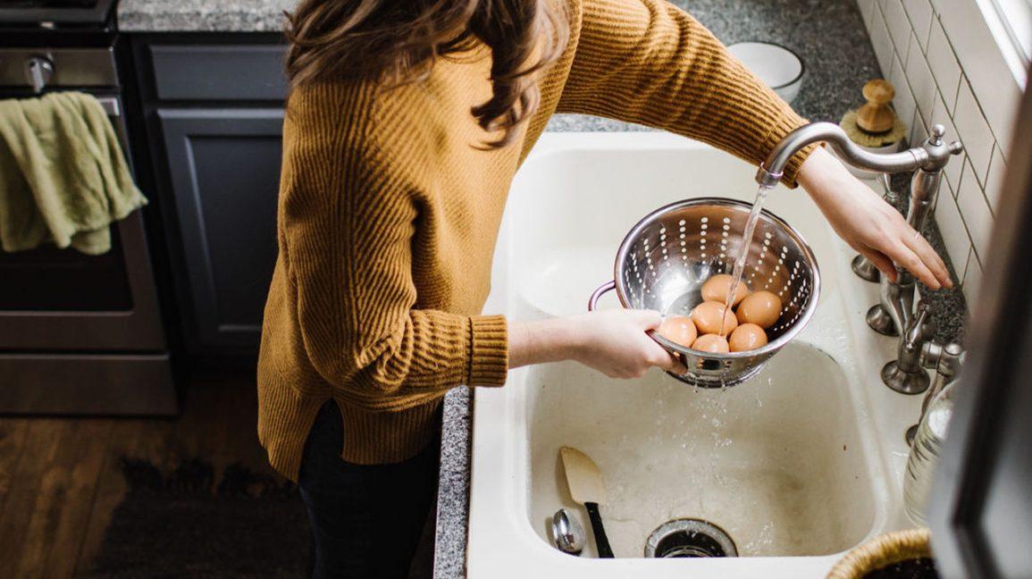 Une femme refroidissant des œufs à la coque dans l'évier