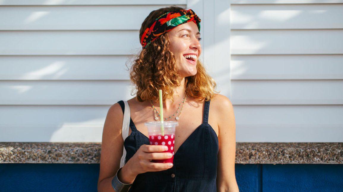 Une femme avec une boisson rouge et froide