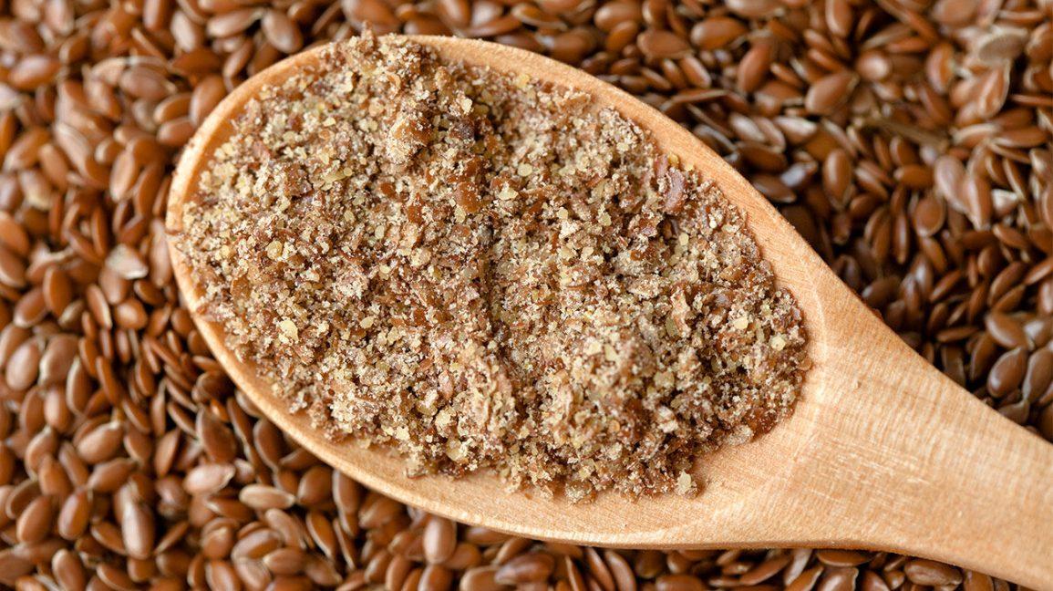 Graines de lin et une cuillère en bois avec des graines de lin moulues