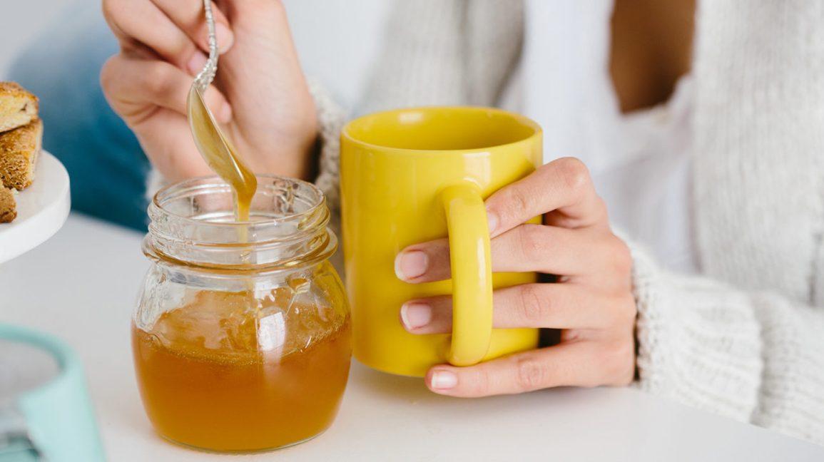 Café au miel Femme ajoutant du miel à son café Café au miel