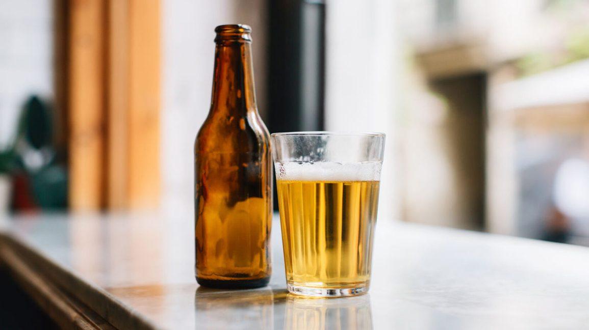 bière en verre avec bouteille vide