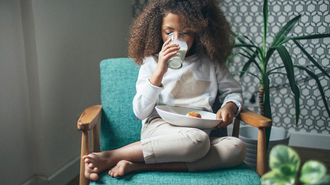 Jeune fille prenant un en-cas et buvant du lait