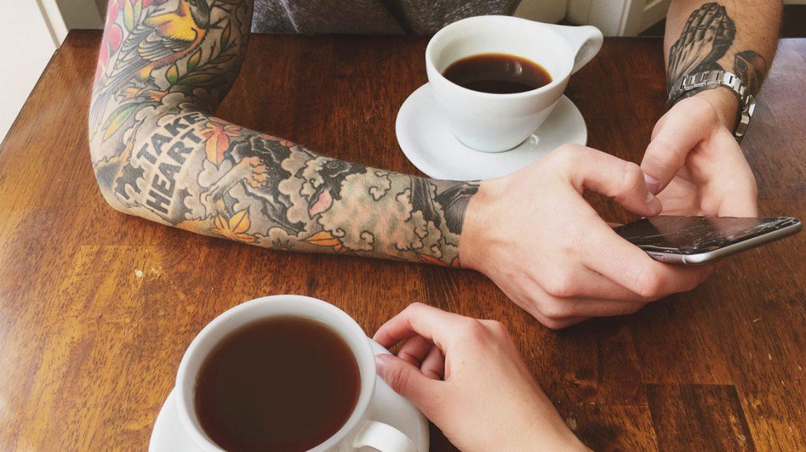 personne tatouée, boire du café à une table