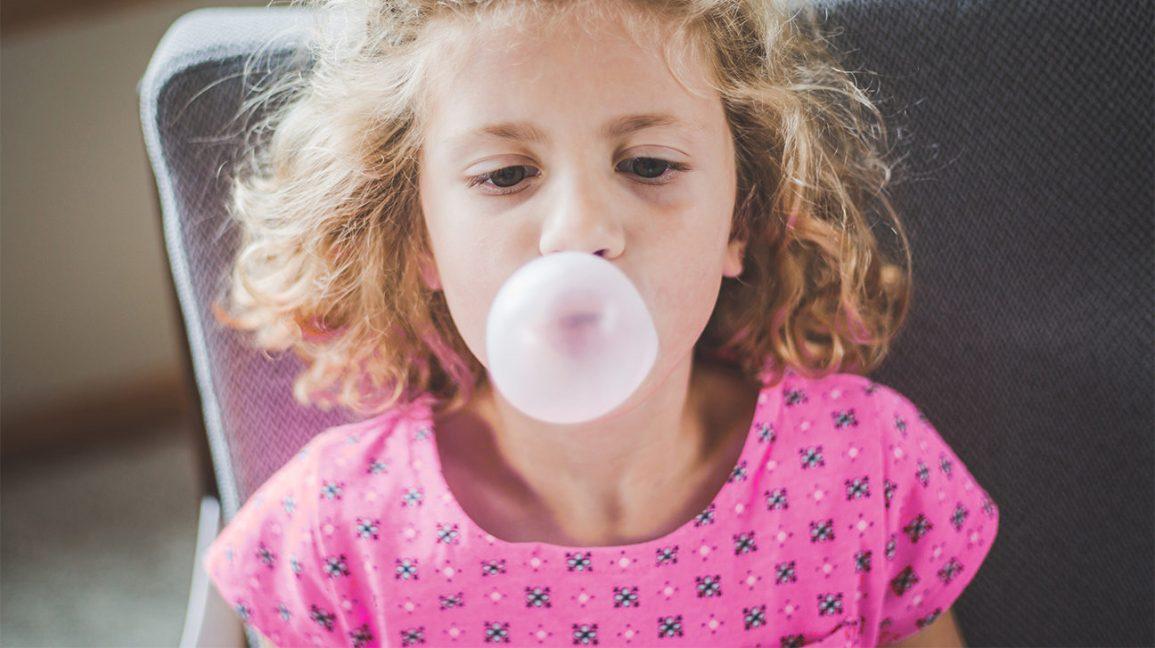 Une fille faisant une bulle de bubble-gum Dioxyde de titane