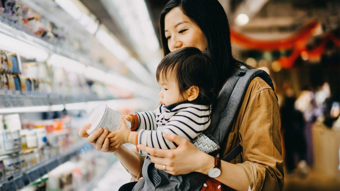 Mère avec jeune enfant à la recherche d'aliments fonctionnels au supermarché