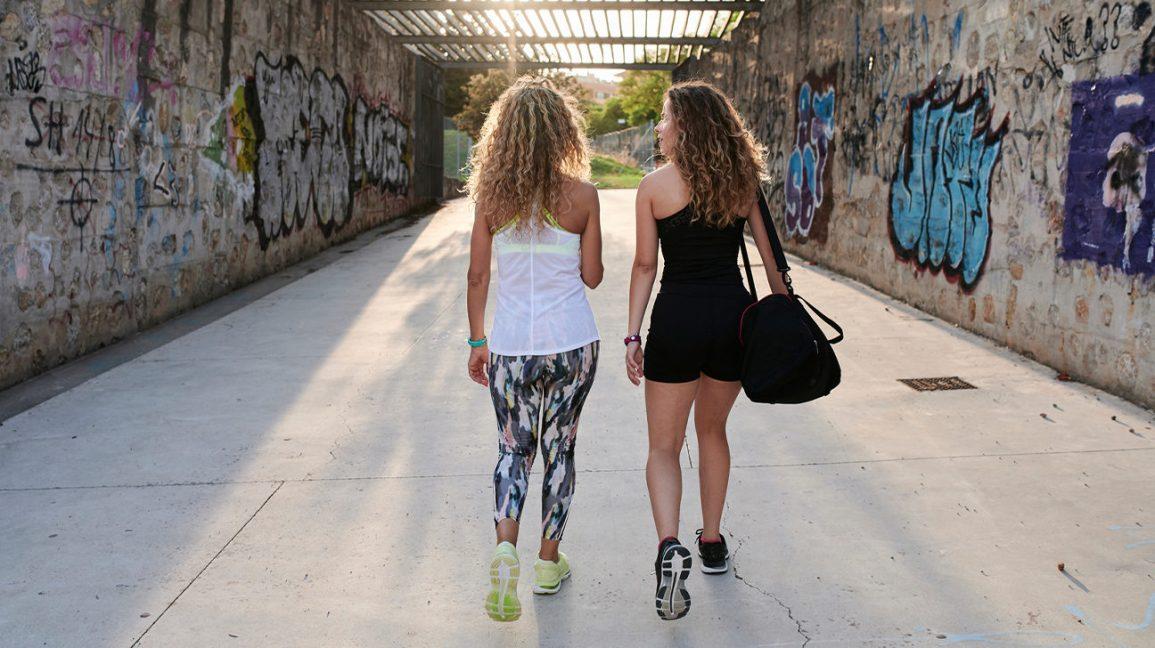 deux femmes marchant dans un couloir ensoleillé