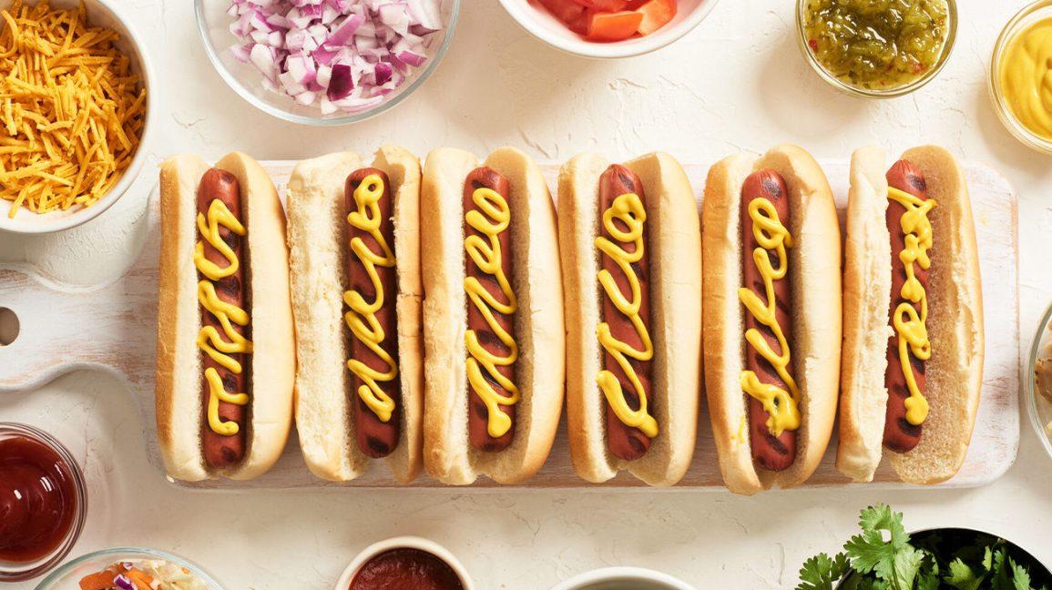 Six hot-dogs sur une table entourée de condiments