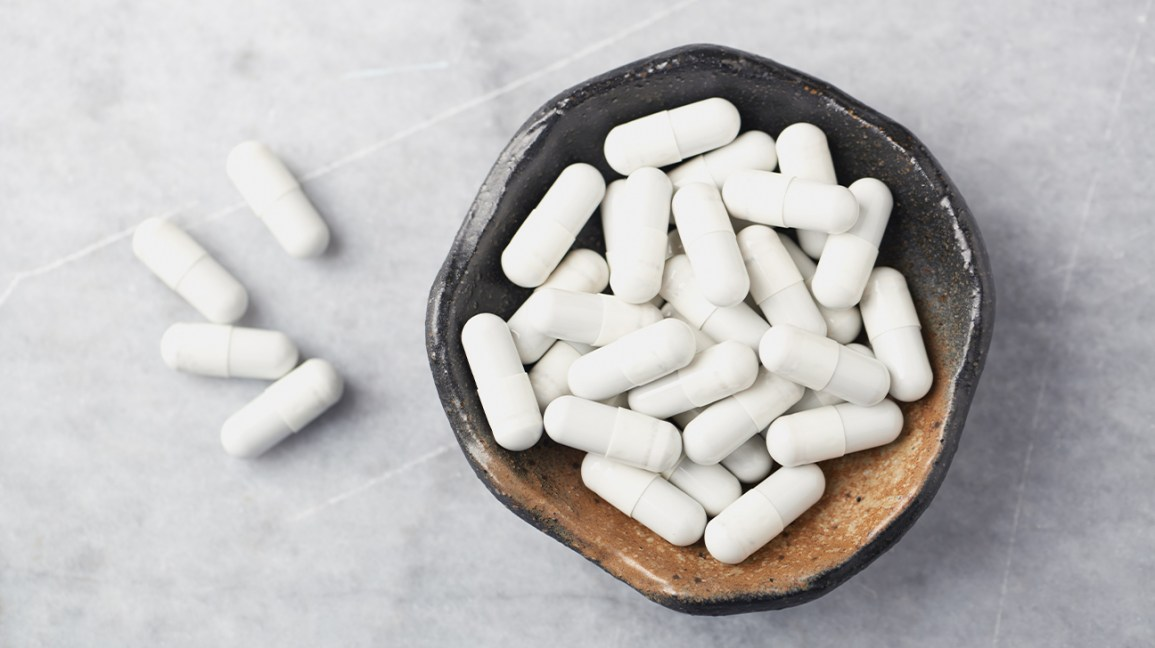 Petit bol avec des capsules de supplément de collagène