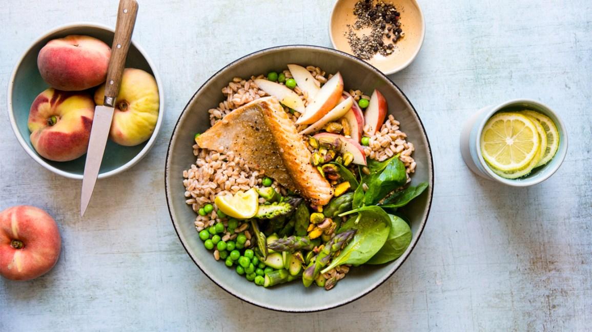bol de grains entiers avec légumes, saumon et pêches