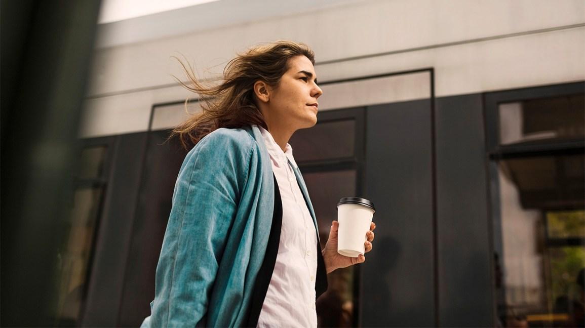 Personne qui marche avec une tasse de café à emporter