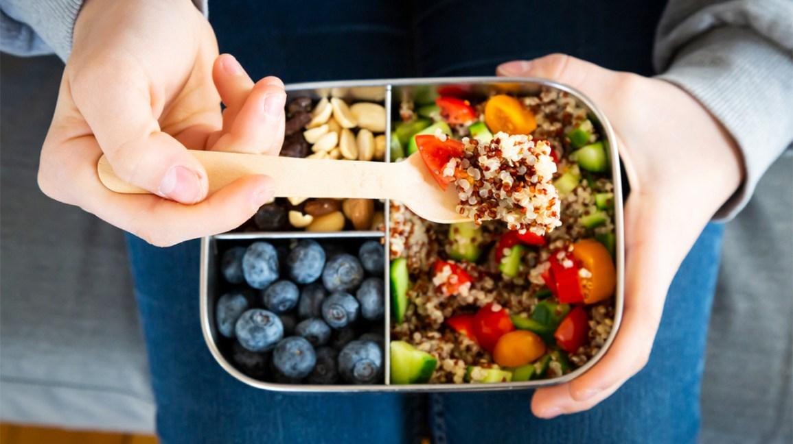 une fourchette de salade de quinoa avec une boîte à lunch compartimentée