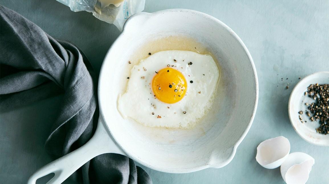 oeuf au plat avec du poivre concassé dans une poêle
