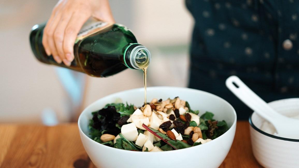 Personne versant de l'huile d'olive sur une salade