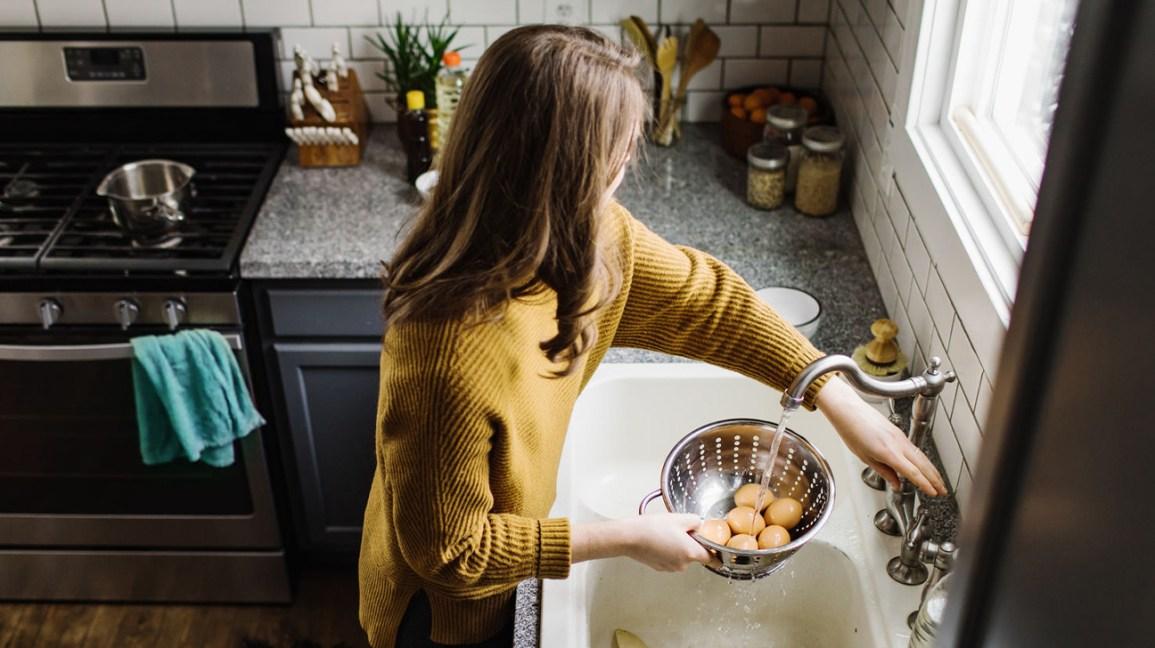 une femme rincant des œufs durs
