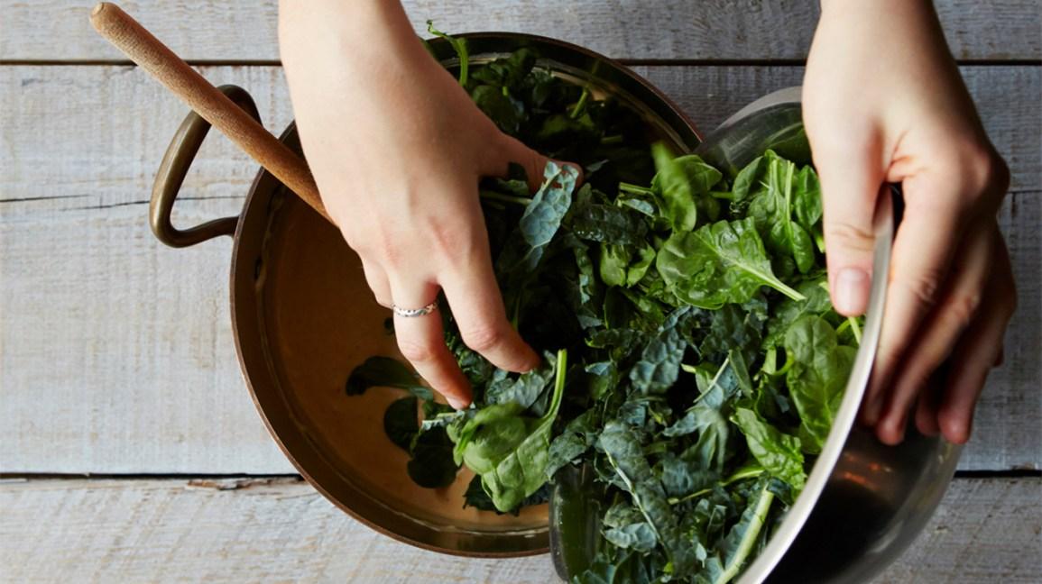 mains ramasser le chou frisé cru et les épinards dans un bol