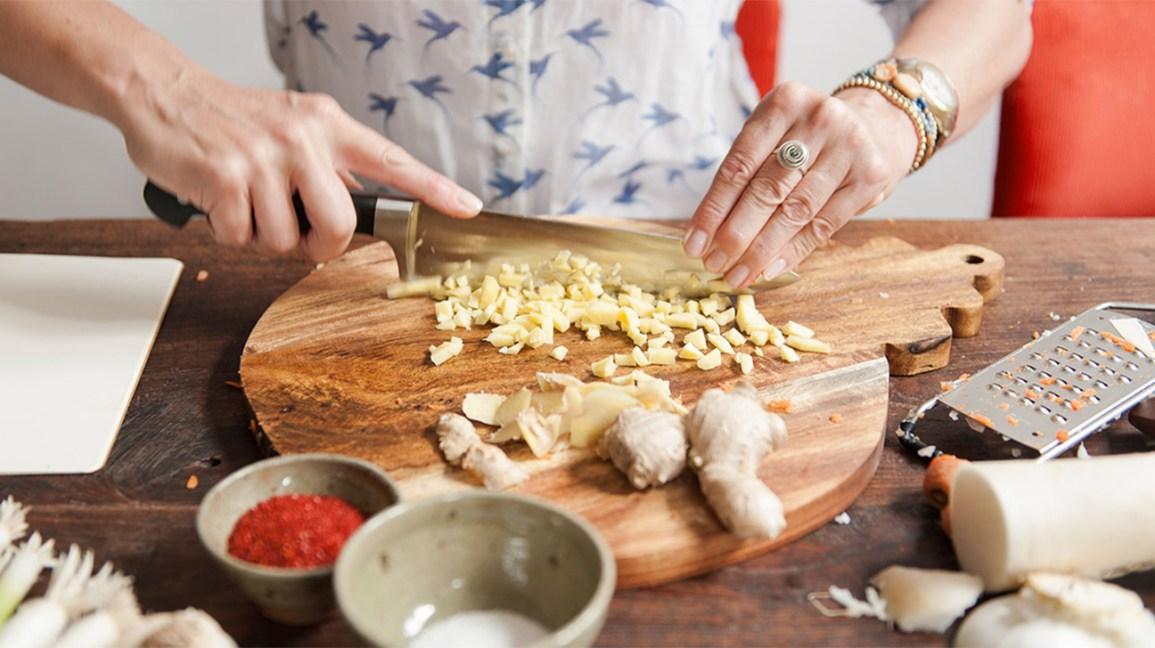 Femme hacher la racine de gingembre cru sur une planche à découper en bois