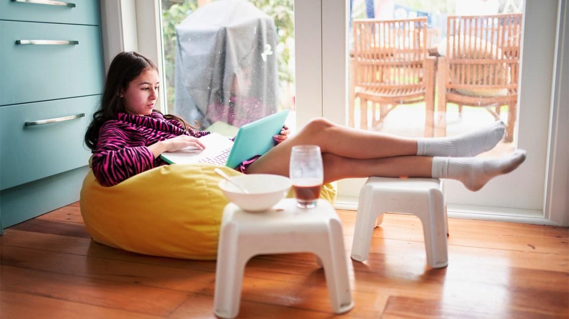 Adolescente sur son ordinateur portable avec collation à proximité