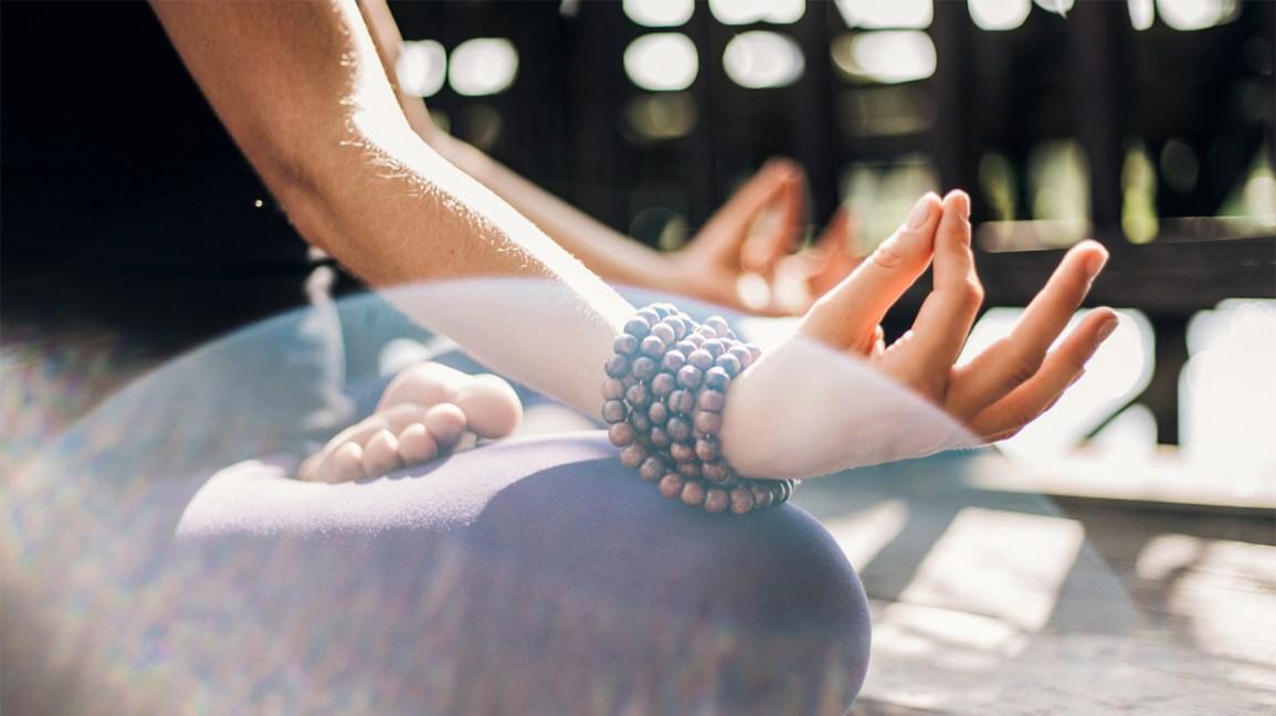 quelqu'un méditant avec un bracelet de perles