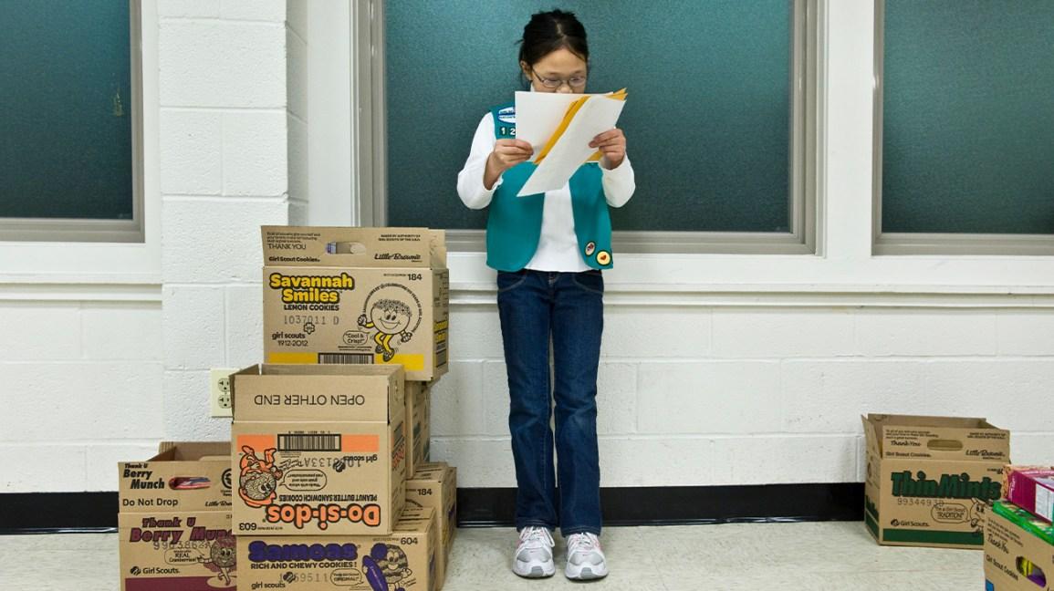 Girl Scout à plus de commandes près de boîtes de cookies