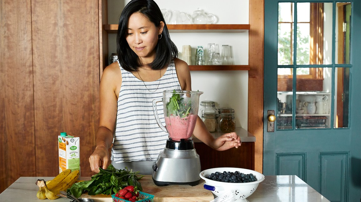 Woman making smoothie avec fruits et légumes frais et surgelés