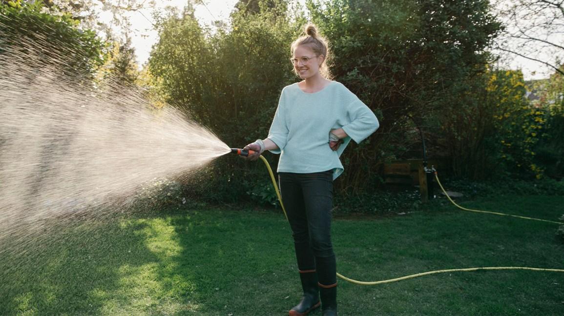 femme à l & # 39; extérieur avec tuyau d'arrosage des plantes