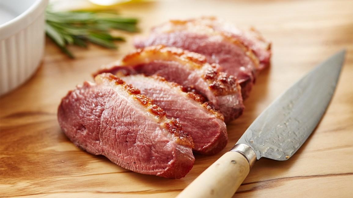 Tranches de viande de canard crue sur une planche à découper