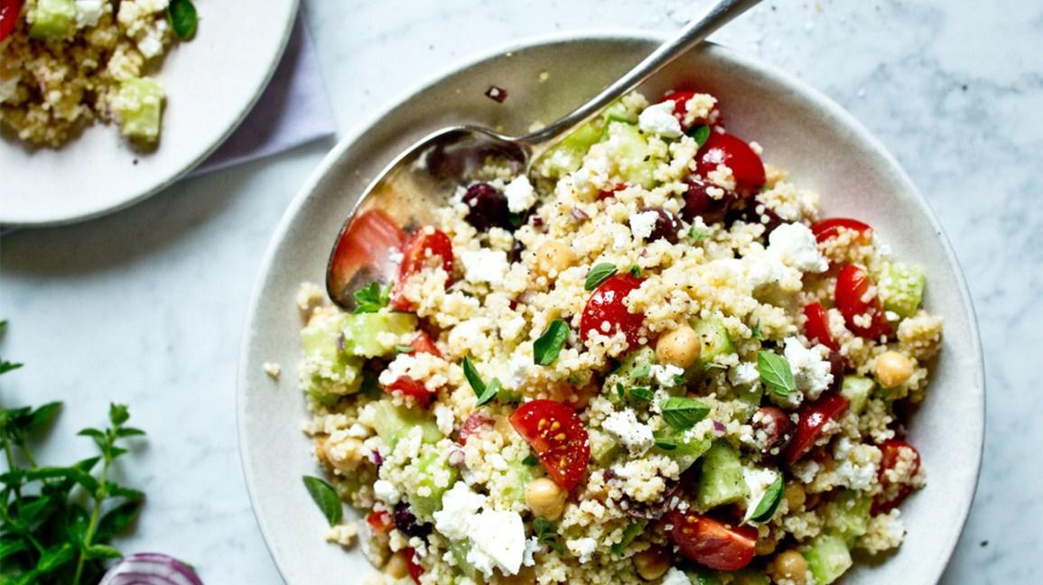 un saladier frais avec couscous, tomates, basilic, olives et feta