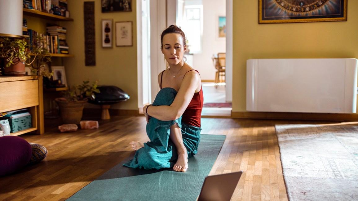 une femme qui fait des étirements sur un tapis à la maison