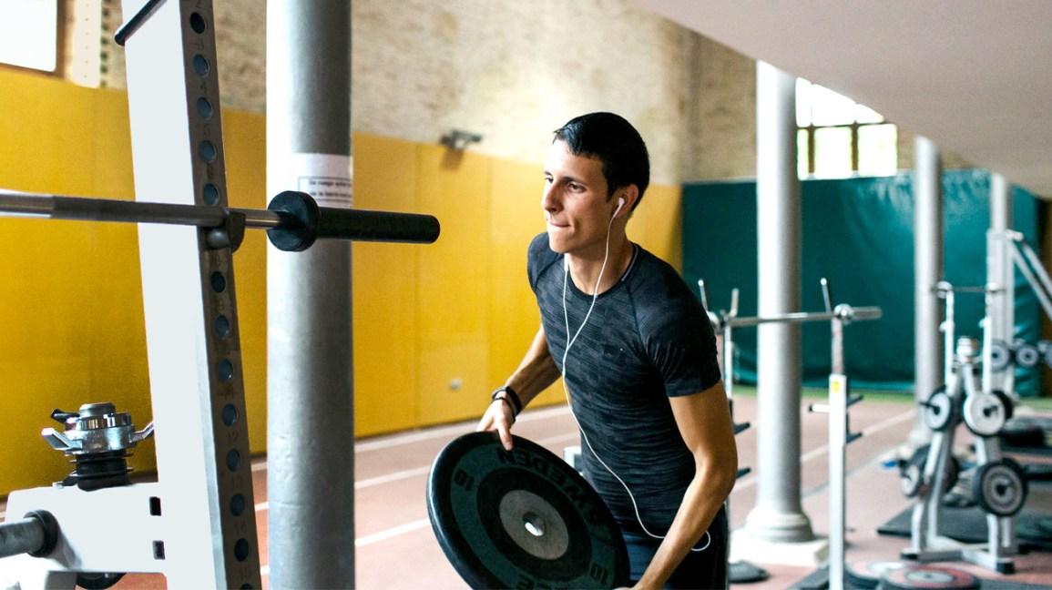 homme, mettre du poids sur haltères dans une salle de sport