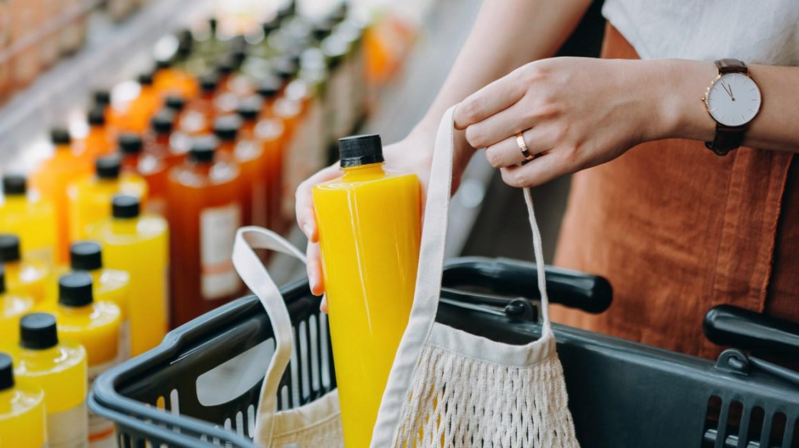 Femme mettant une bouteille de jus dans un sac dans un magasin