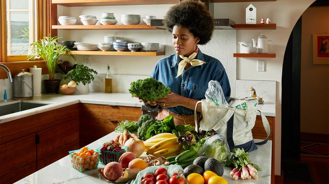 Femme regardant des aliments sains qu'elle a achetés