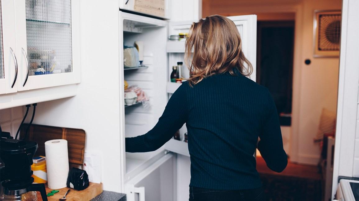 Personne atteignant quelque chose dans le réfrigérateur