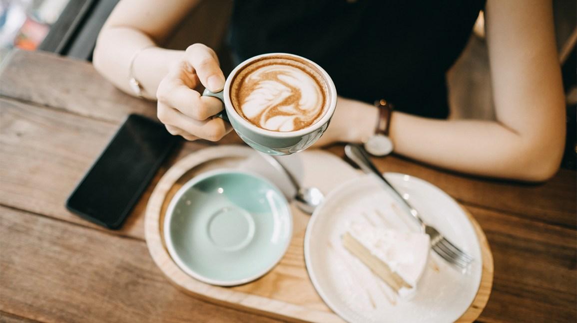 Femme appréciant une tasse de café et un gâteau