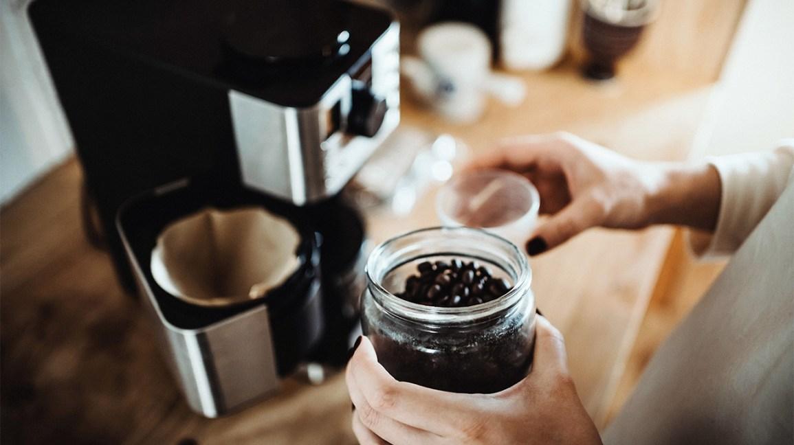 Une personne qui prépare des grains de café pour un moulin