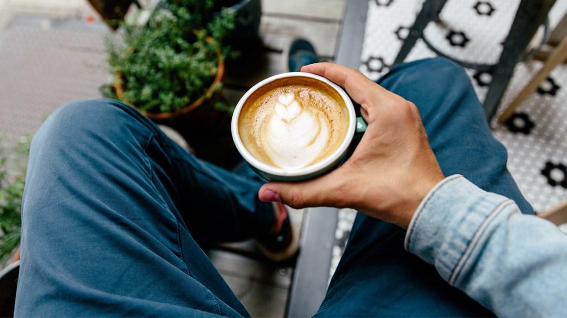 Homme tenant un verre de café