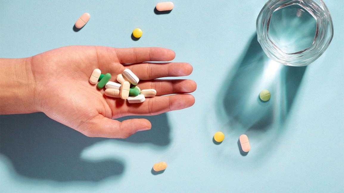 pilules et suppléments assortis dans une paume ouverte