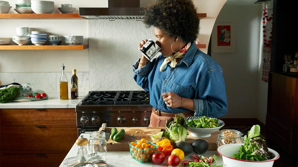 Cétose : Femme buvant dans une tasse et debout près d'une table contenant des tomates et d'autres produits