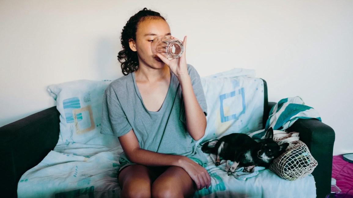 Femme assise dans un canapé de l'eau potable