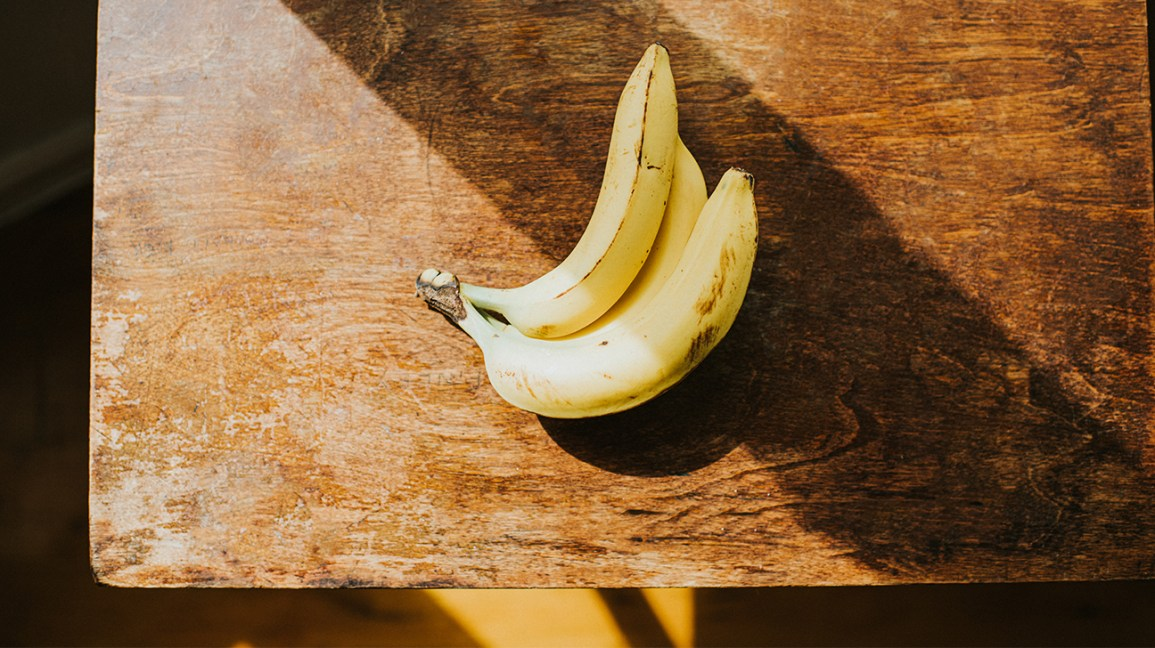 trois bananes sur une table en bois
