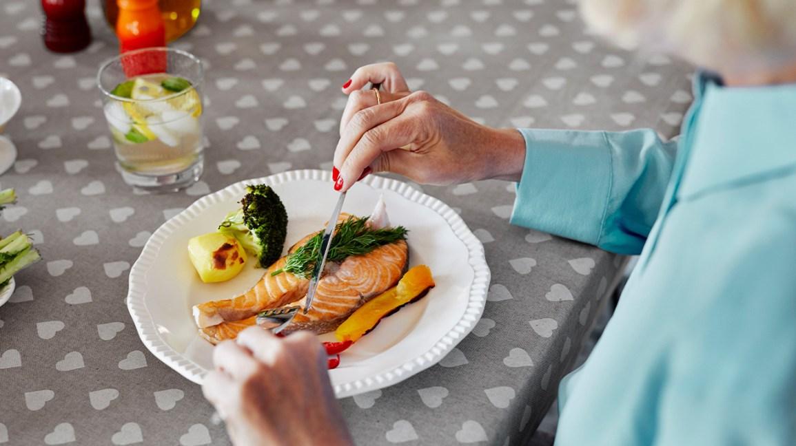 femme plus âgée, manger du saumon et des légumes