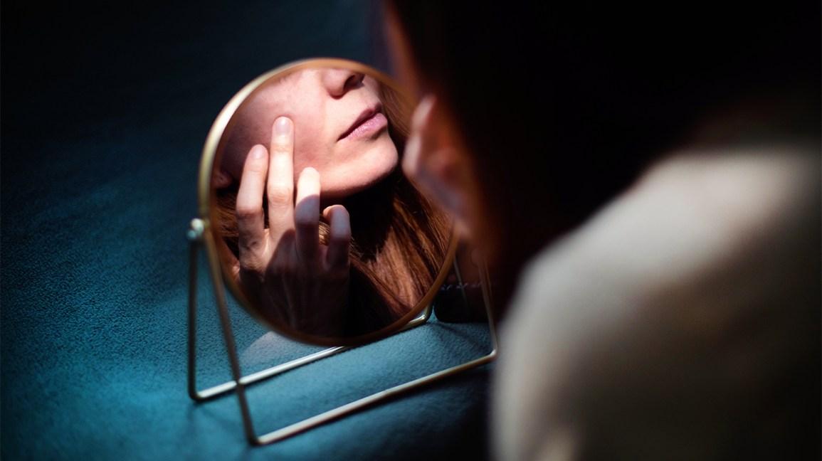 Derma Drink : Femme regardant son menton dans un miroir de beauté