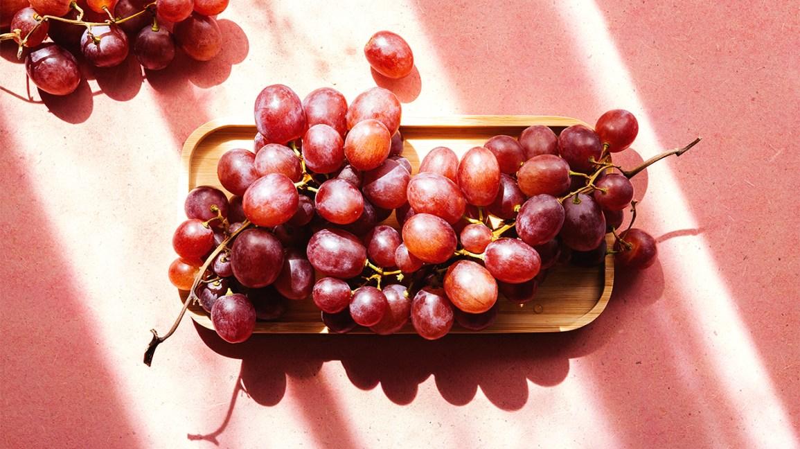 une grappe de raisin sur un plateau en bois