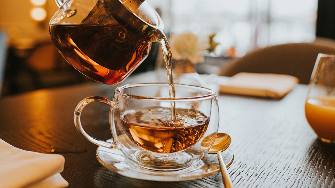 thé Yogi DeTox : Bouilloire versant du thé dans une tasse transparente sur une table