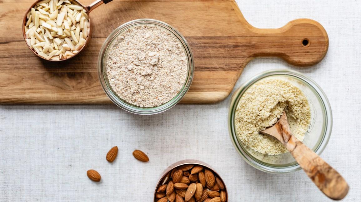 Farines Keto-Friendly amandes et farine d'amande sur une planche à découper