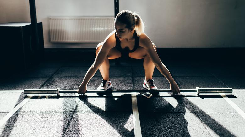 femme soulevant des haltères sans poids supplémentaires