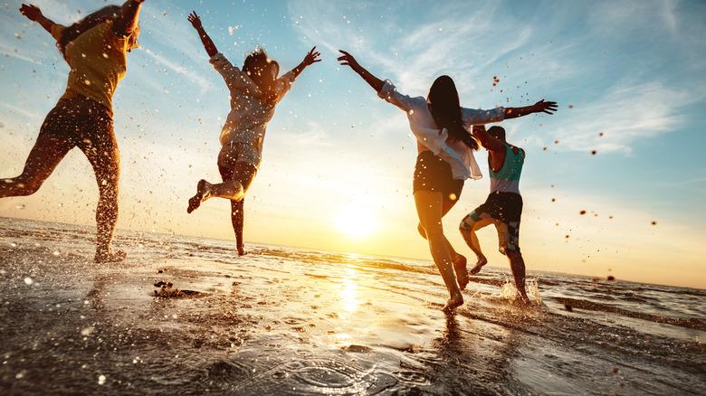 gens heureux qui courent sur la plage