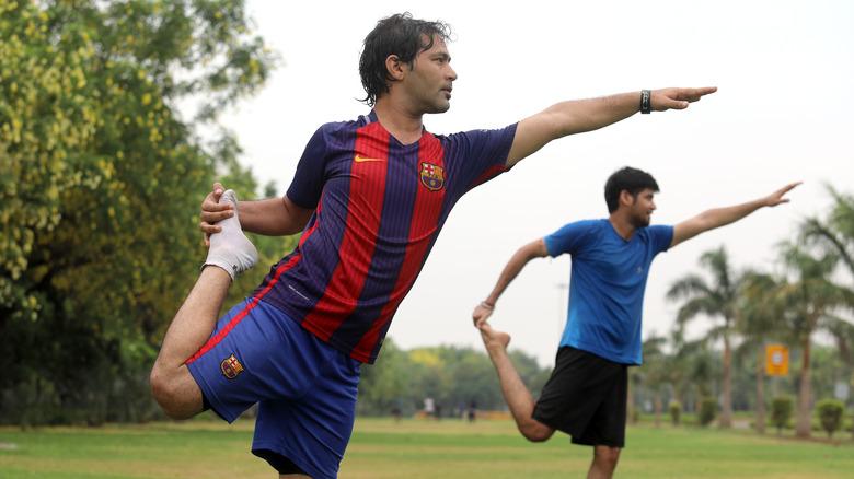 hommes en équilibre sur une jambe