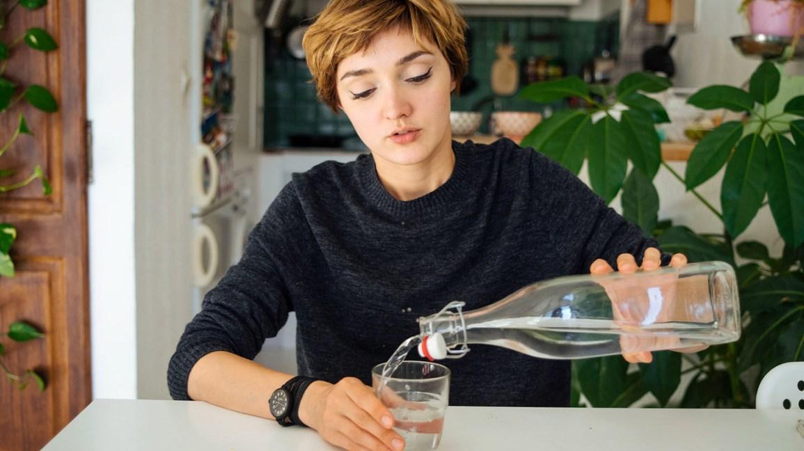 femme versant de l'eau d'une bouteille en verre